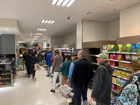 a long queue of people in a supermarket aisle. The queue stretches right down the ailse into the distance. People look bored.