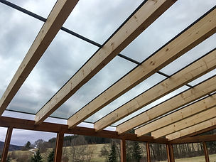 The detail of the transparent glass roof of the wooden pergola. .jpg