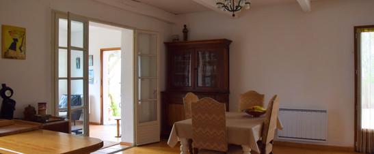 Living waar je de eettafel ziet en een kast waar glazen in staan.