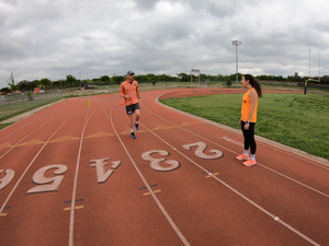 Track demonstrating run drill to athlete