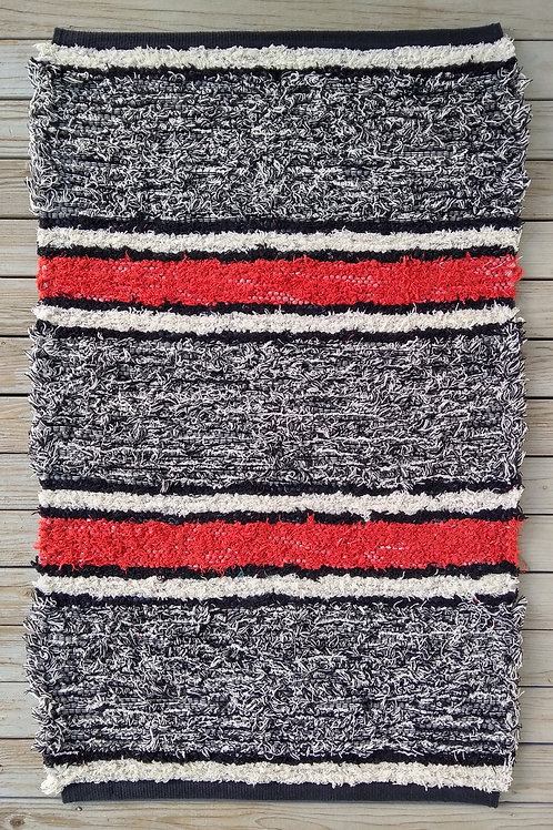 Handwoven rug with black, white, and coral stripes