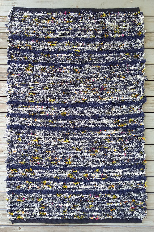 Handwoven rug with dark blue and white stripes and color accents