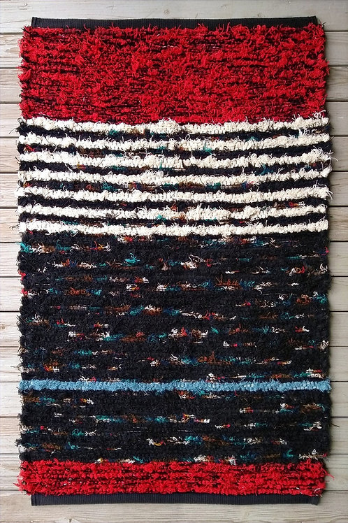 Handwoven rug in red, white, black and turquoise