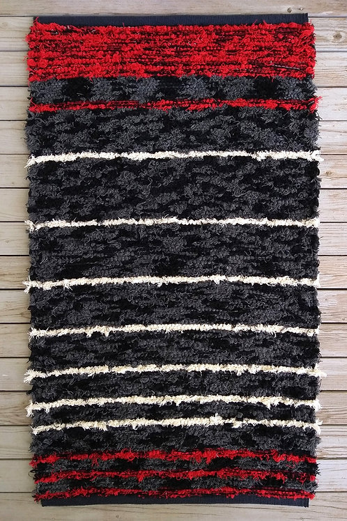 Handwoven rug with black, gray, red, and white stripes