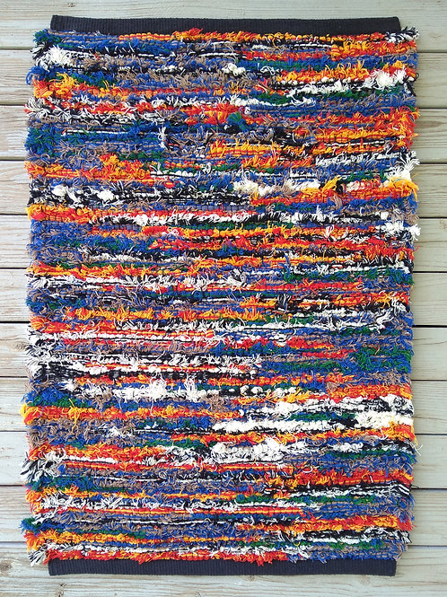 Handwoven rug in blue, orange, yellow, and white