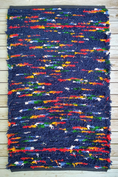 Navy blue handwoven rug with red, yellow, green, and white accents