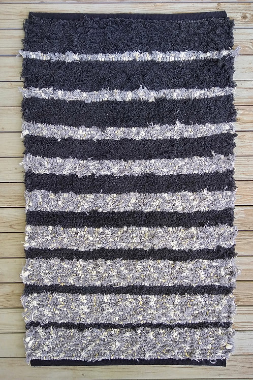 Handwoven rug with black and gray stripes