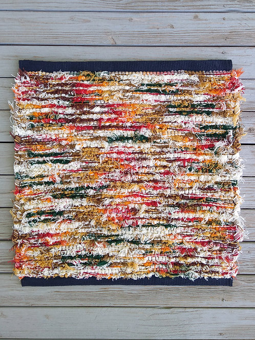 Handwoven rug in gold, tan, cream, yellow, orange, and red