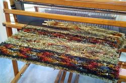 Weaving a rug on my antique floor loom.