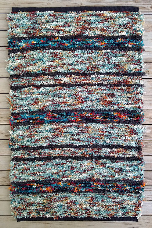 Handwoven rug in aqua, turquoise, and gray stripes with color accents