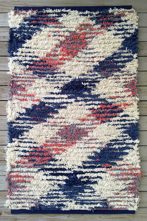 Handwoven rug in blue, white, and pink