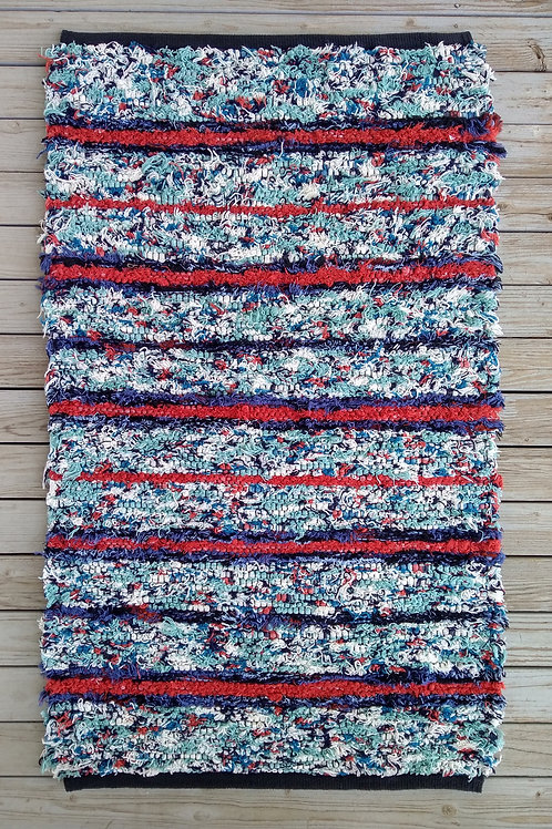 Handwoven rug with turquoise, blue, and coral stripes