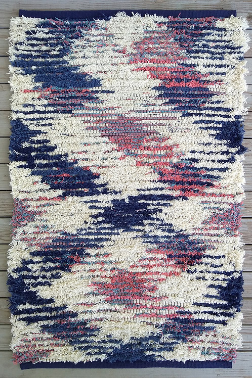 Handwoven rug in blue, pink, and white
