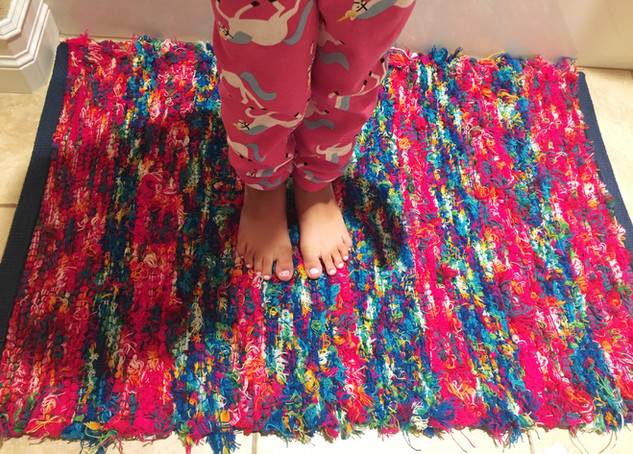 """""""This little one is genuinely grateful for Kathy's rug, a comfortable, warm place for these small feet. At a young age, the kid already has an appreciation for the fine craft of a local artisan."""" -Dawn B."""