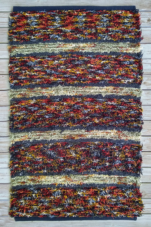 Handwoven rug in brown, rust, sage, and gray