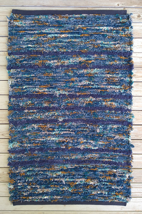 Handwoven rug with blue, turquoise, cream, and rust stripes