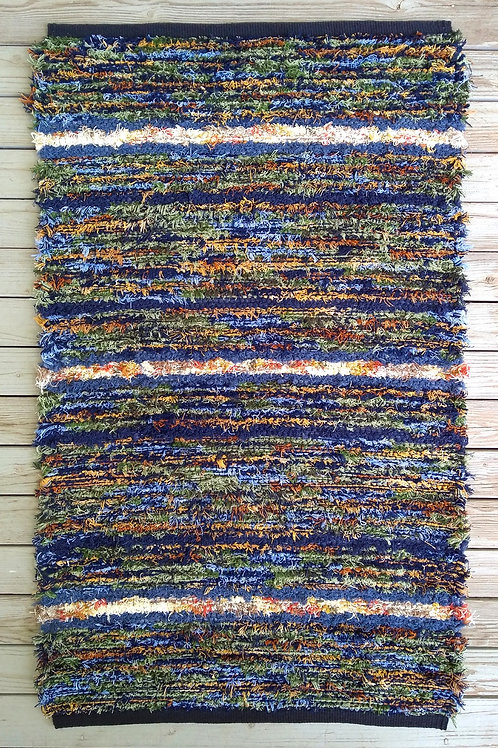 Handwoven rug in blue, green, gold, and cream