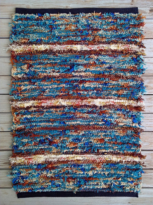 Handwoven rug in blue, brown, rust, and cream