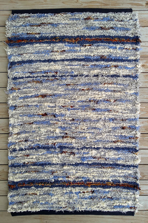 Handwoven rug in blue, gray, white, brown, and rust