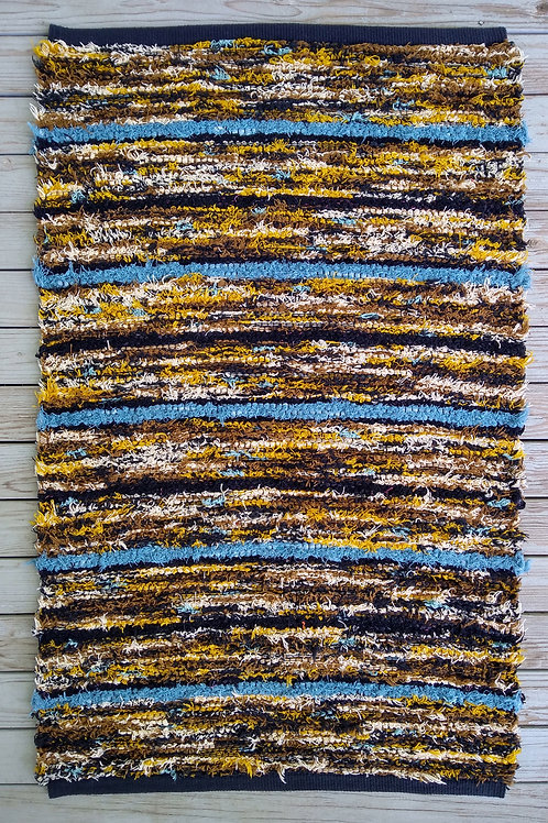 Handwoven rug with brown, gold, black and turquoise stripes