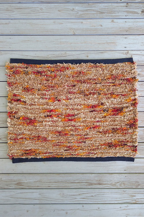 Small handwoven rug in gold, tan, cream, yellow, orange, and red