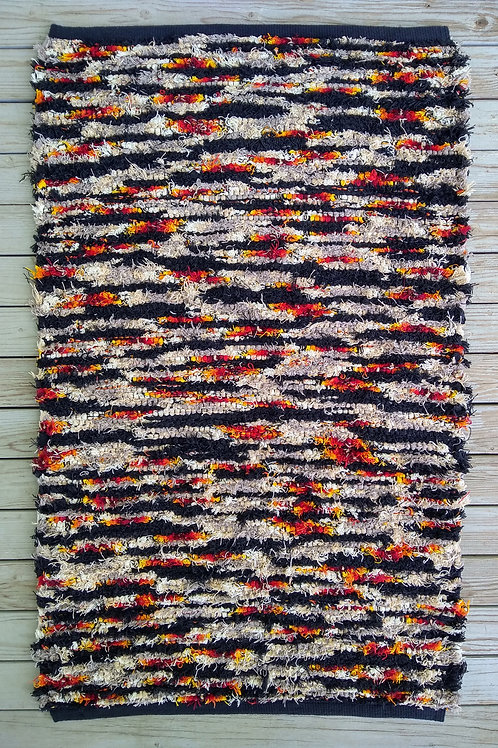 Handwoven rug in black, tan, red, and orange