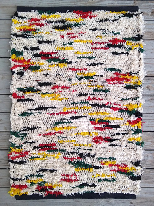 White handwoven rug with red, yellow, green, black accents