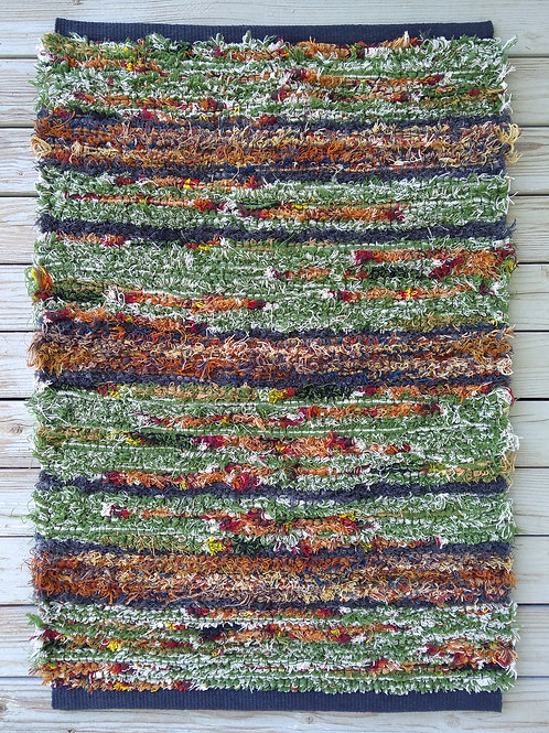 Handwoven rug in green, brown, and gray
