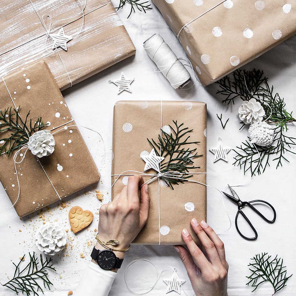 Modern and minimal Christmas holiday wrapping with brown paper on gifts lay amongst pine cones and sprigs of branches tied with twine.