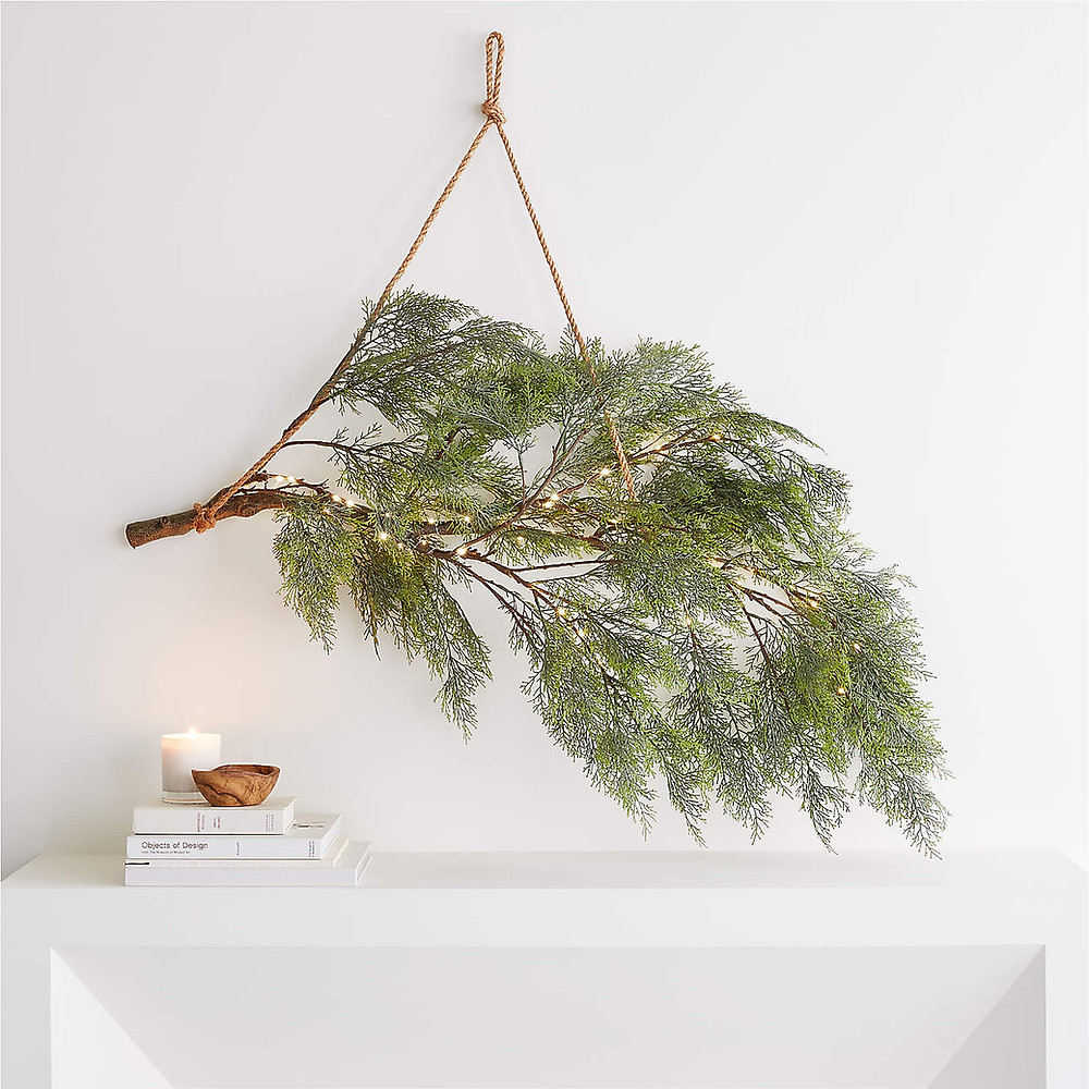 A minimal and modern Christmas wreath as a branch hung from twine above a white fireplace mantel in Scandinavian nordic decor style.