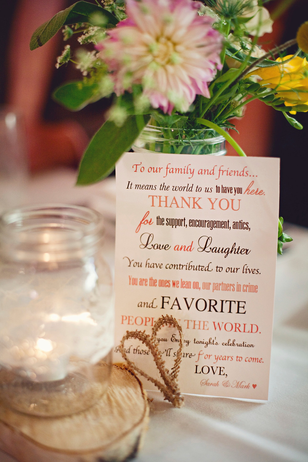 A thank you note sits on a table set at a rustic Italian inspired wedding with romantic garden flowers, wooden rounds, and mason jars wrapped with lace awaits guests.