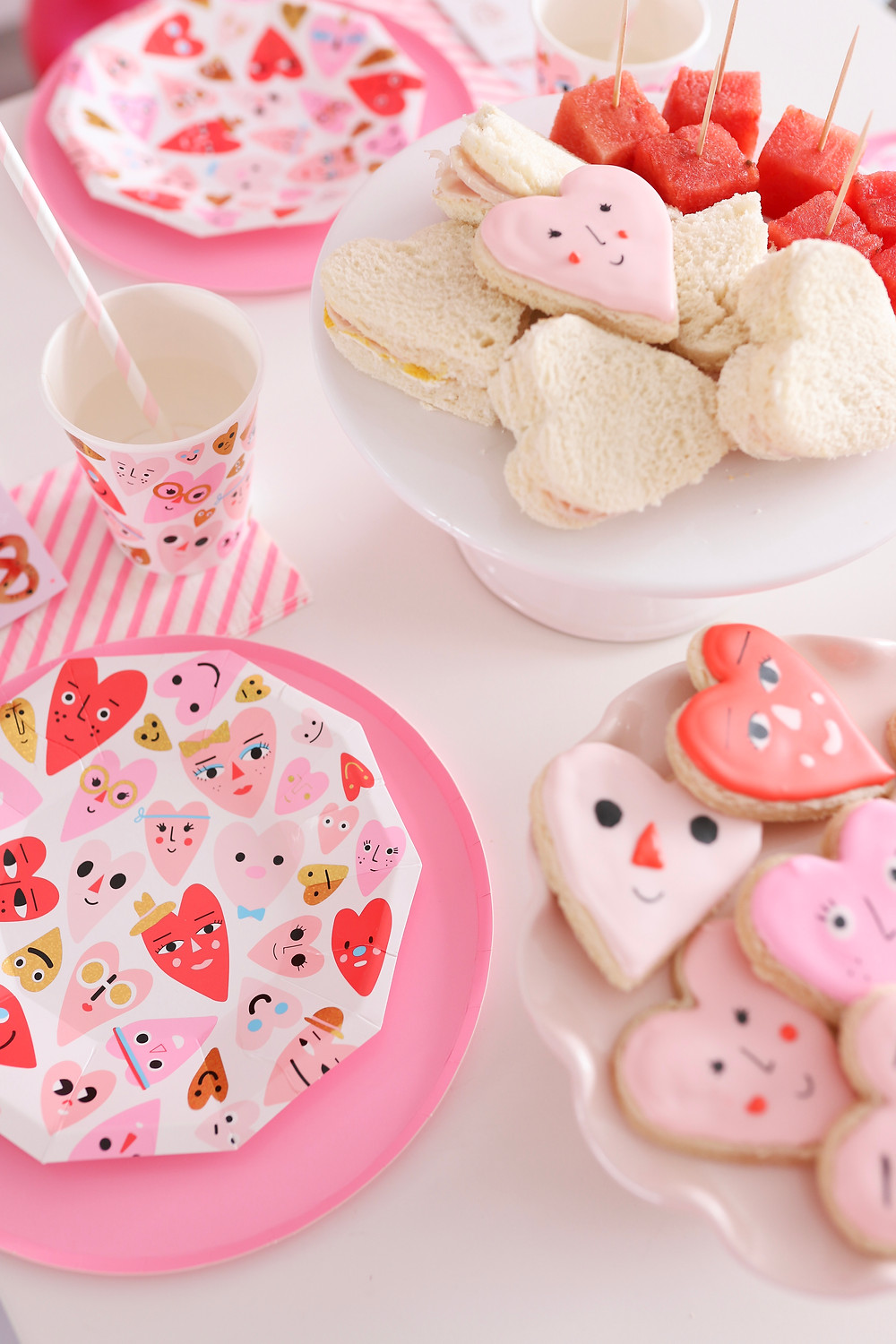 Valentines Day cookies, snacks and plates on a table.