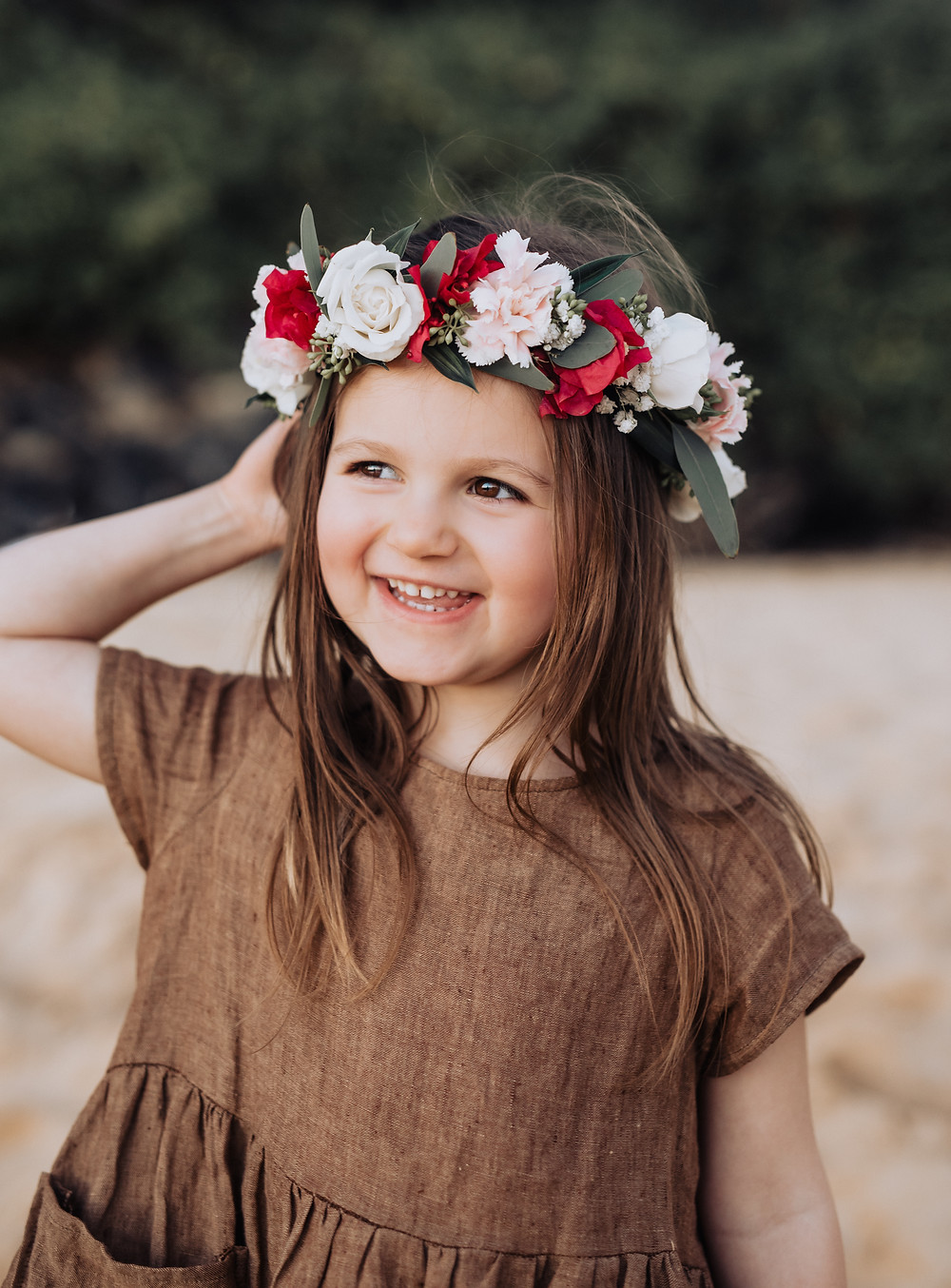 Little girl smiling with a flower lei in her hair.