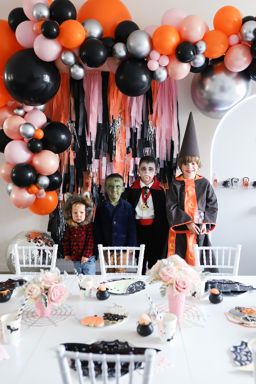 A kids Halloween party with children dressed up in a red lumberjack bear, Frankenstein, Dracula and a wizard costume getting ready to sit at the children's white table set up with pink roses, black bat paper plates and pumpkin decorations.