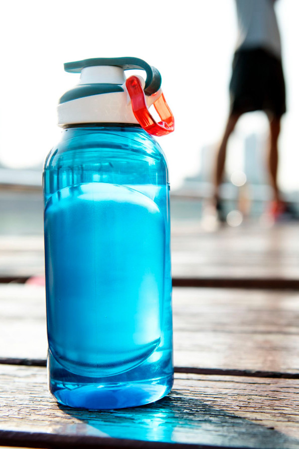A blue reusable water bottle sitting on the ground.