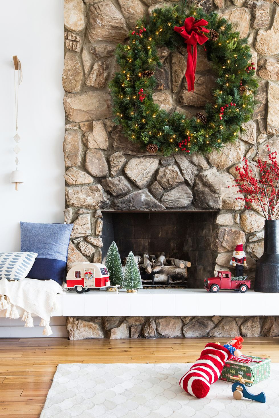A traditional stone Christmas holiday fireplace decorated with a green wreath, miniature cars and bottle brush trees for a stylish and cozy feel.