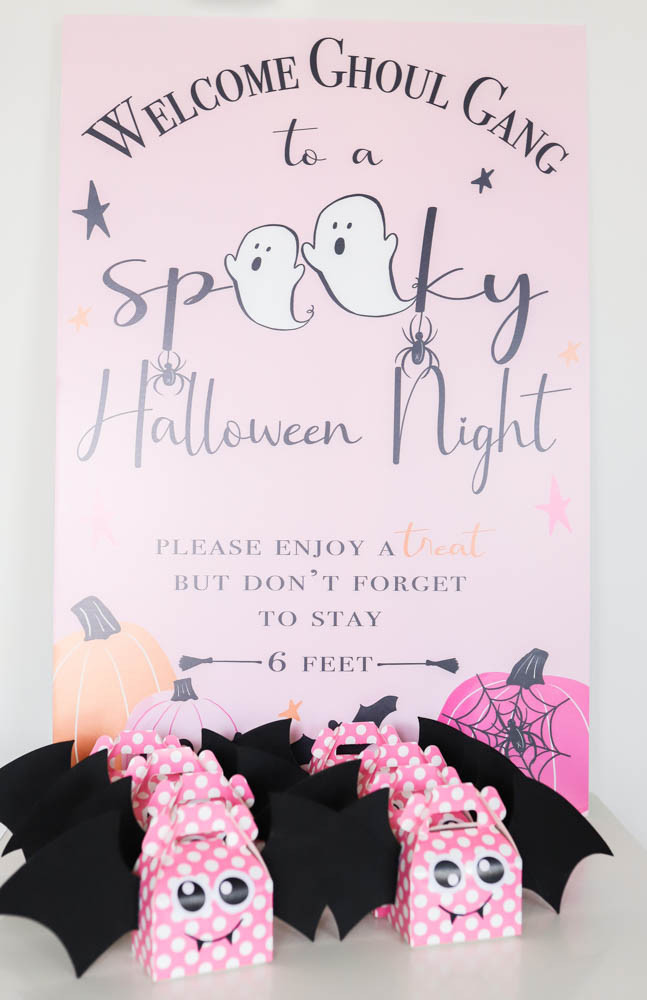 A social distance kid's halloween party with a pink invitation that has pink polka dot bat treat bags in front of orange and pink pumpkins covered in a spider on his spiderweb.