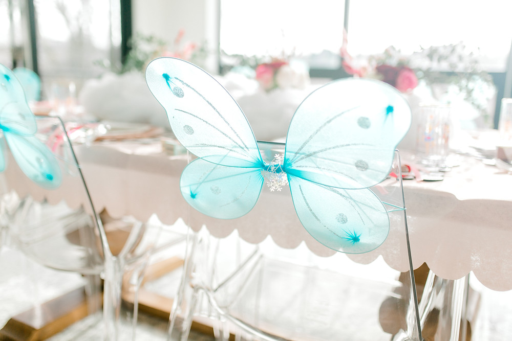 Table decorated with floral centrepieces, nutcrackers and blue butterfly wings.