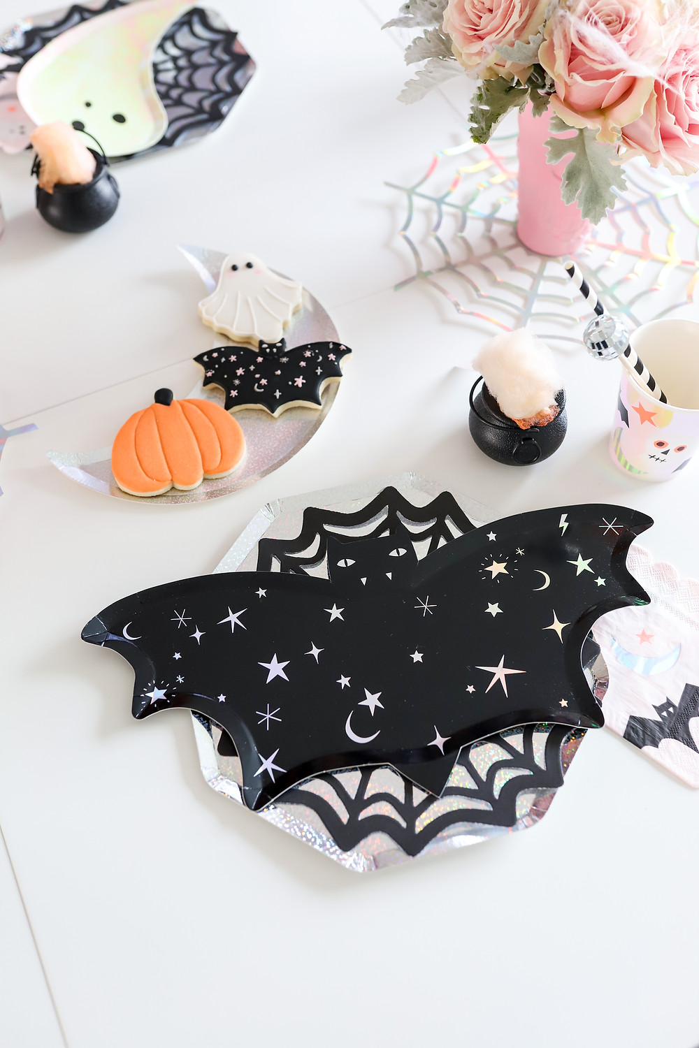 Spooky Halloween treats and decorations for kids party with scary ghost, bat, pumpkin, cauldron and metallic spider webs holding a pink vase with pink roses.