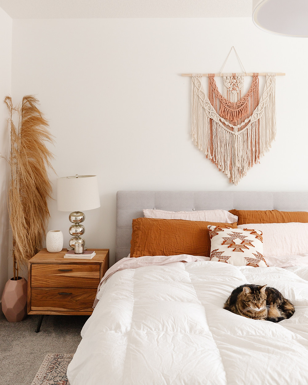 Cream and blush macrame wall hanging over bed with grey fabric headboard wood side table with silver lamp cat sleeping on white duvet pampas grass in pink vase on floor