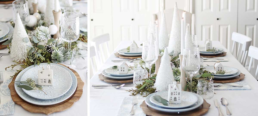 A white Christmas tablescape done on a wooden white table with white bottle brush trees, live greenery, white candles in a minimal simple style.