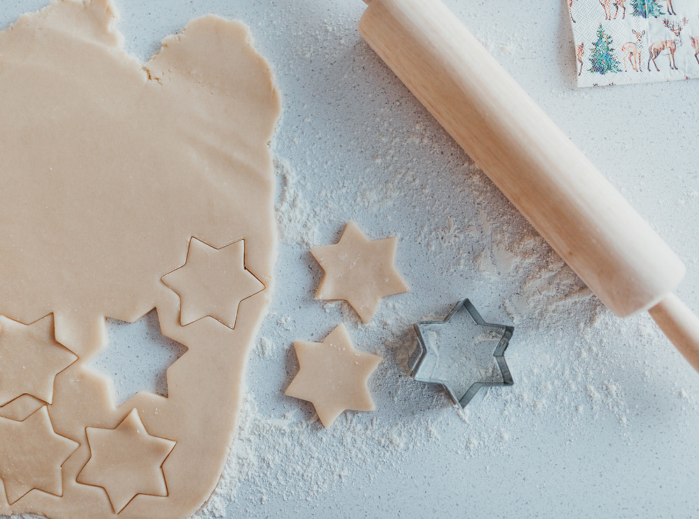 Some rolled out cookie dough, a rolling pin and a star shaped cookie cutter on a counter.