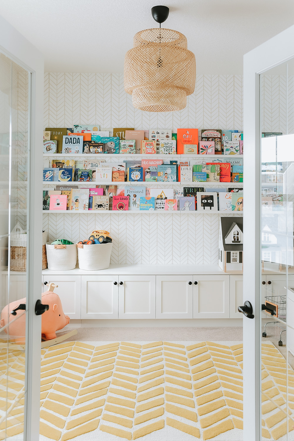 adorable book shelf lining wall in childrens room with wallpapered walls and chevron patterned area rug on floor