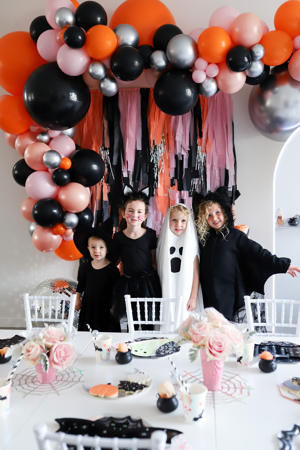 A Halloween party for kids with diy ghost, witch, and cat costumes standing in front of pink, orange, and black balloon streamers arched over the wall, as well as a metallic disco ball behind a white table decorated with pink roses and spooky decor.