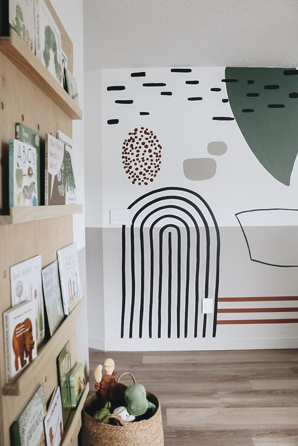 A hand painted wall mural idea for a children's playroom with simple wooden bookshelves and woven storage baskets below a bookshelf.