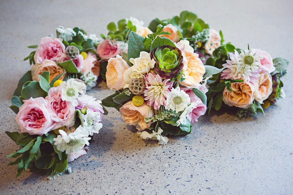 Wedding bouquets of fresh romantic flowers laying together.