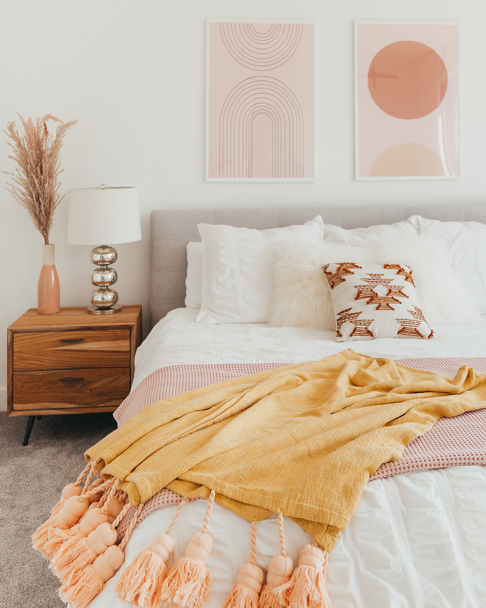 blush colored framed art pair above grey fabric headboard white sheets and duvet pink and yellow throws on bed wood side table with silver table lamp pink vase with pampas grass
