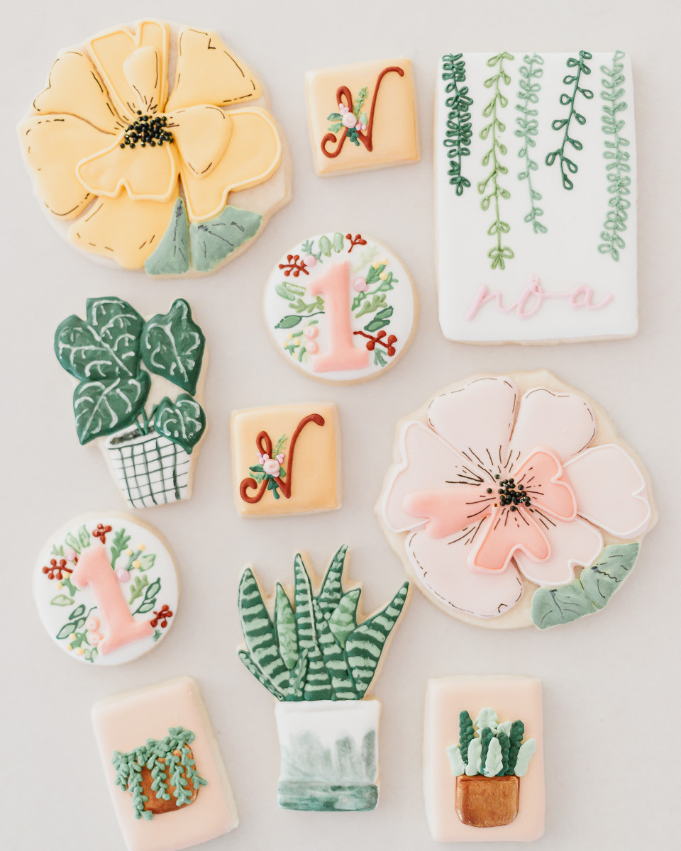 A pile of carefully decorated cookies in the shape of flowers and plants.