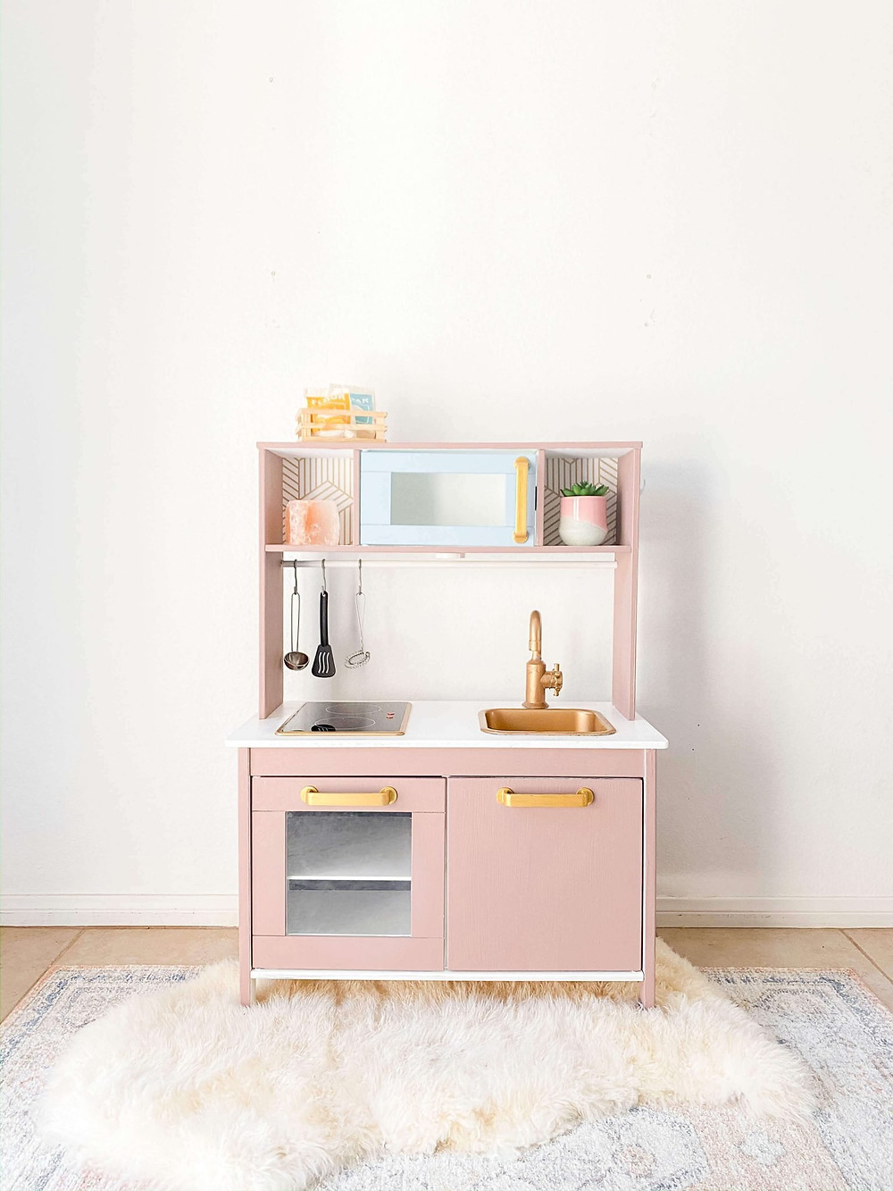 A little girls pink IKEA play kitchen in simple playroom against white wall on hardwood floor with furry area rug