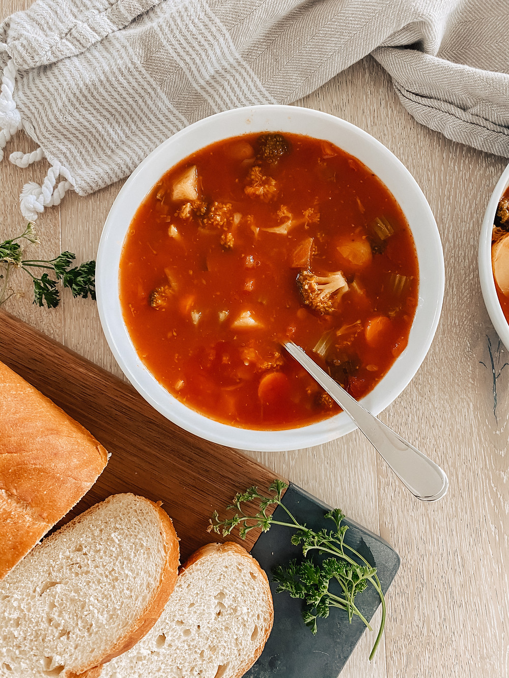 A bowl of hearty vegetable soup sits on the table surrounded by a grey tea towel, sliced bread and fresh herbs.